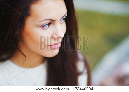 Portrait of young pretty brown-eyed women brunettes on beautiful blurred background closeup