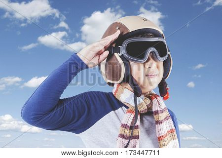Picture of a cute boy wearing an aviator helmet and showing a saluting gesture shot outdoors