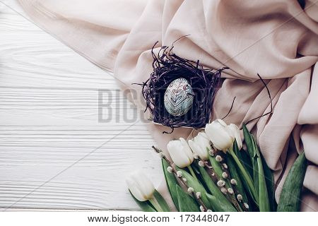 Stylish Easter Egg With Floral Ornaments In Nest On Beige Fabric And Tulips And Willow Buds On Rusti