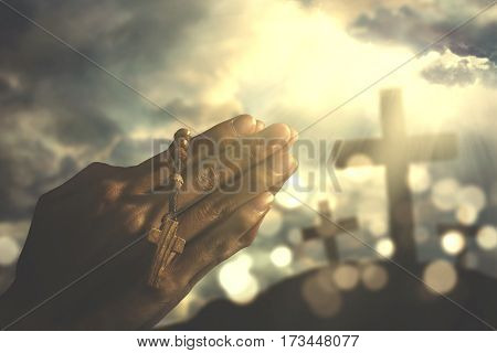 Image of hands of devout person praying to the GOD while holding a rosary with crucifix symbol