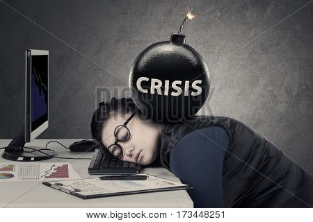 Portrait of young entrepreneur feels tired with a bomb of crisis over her head while sleeps on the keyboard