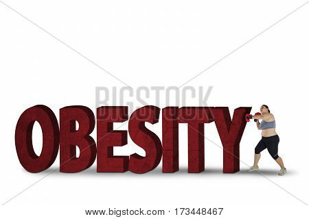 Fat woman wearing boxing gloves while fighting with stones shaped word of obesity on the studio