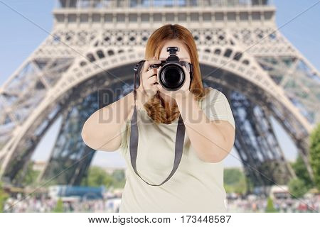 Portrait of fat woman using a camera to take photos while standing near the Eiffel tower