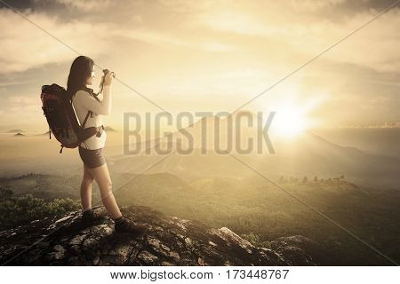 Image of young woman photographer is taking photo while standing on the mountain peak