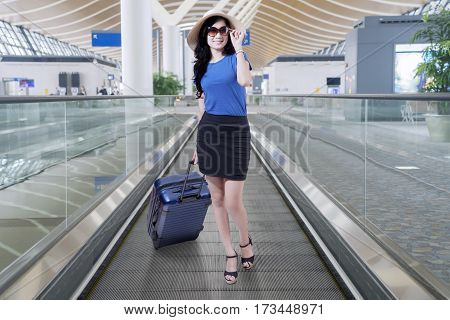 adult airport arrival asian attractive bag baggage beautiful carry chinese corridor departure entrepreneur female flight full gate hair hallway hat hispanic hold indian indonesian japanese journey length luggage passenger person posing public smiling stan