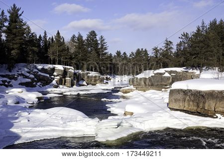 Wide view of a snowy country landscape with a small stream of rapids running through rock faces on either side and a background of green fir trees at Pabineau Falls near Bathurst, New Brunswick on a bright sunny day with blue skies and clouds in February.