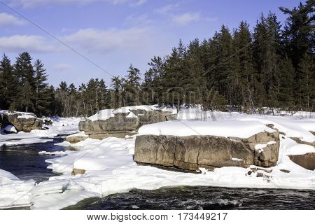 Wide view of a snowy country landscape with a small stream of rapids running through rock faces on either side and a background of green fir trees at Pabineau Falls near Bathurst New Brunswick on a bright sunny day with blue skies and clouds in February.
