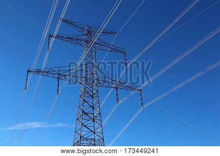high voltage steel pylon against blue sky