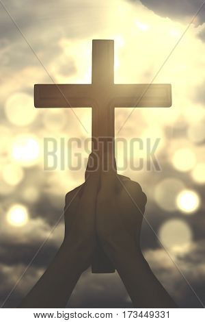 Picture of human hands praying to the GOD while holding a christian cross with bright sunlight on the sky