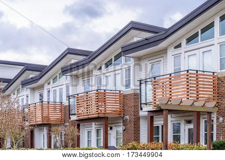 Modern brick and stucco condo buildings with balconies.