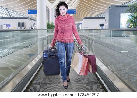 Portrait of Indian female shopper carrying a luggage and paper bags while walking on the escalator