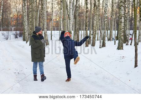 Two friends strolling through the snowy birch forest and talking. One of them slipped and lost his balance waved his hands