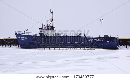 Caraquet, New Brunswick, February 5, 2017 -- Close up of a large shipping boat at the snow covered docks in the frozen waters of Chaleur Bay at Caraquet, New Brunswick on a chilly overcast day in February.