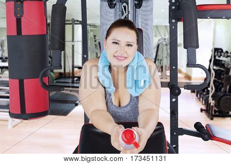 Pretty overweight woman smiling at the camera while sitting on gym equipment after exercise