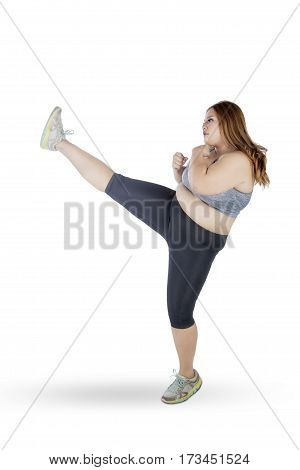 Full length of overweight woman with blonde hair wearing sportswear and doing workout by kicking at copy space