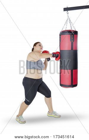 Portrait of overweight blonde woman practices boxing by punching a boxing bag with boxing gloves