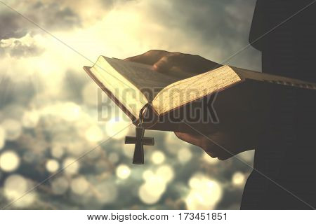 Image of a christian person reading a bible with rosary shot with bright sunlight on the sky