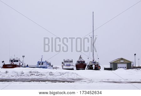 Caraquet, New Brunswick, February 5, 2017 -- Horizontal of fishing boats dry docked for the winter in the snowy land off the frozen waters of Chaleur Bay at Caraquet, New Brunswick, on a chilly overcast day in February.