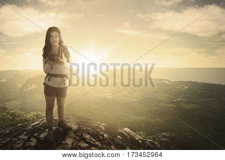 Beautiful woman hiker standing and looking at the camera while holding digital camera on mountain peak at sunrise