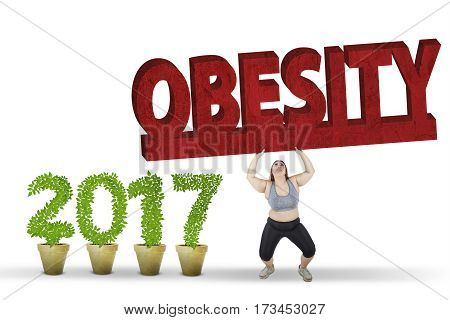 Overweight woman wearing sportswear and lifting obesity text in the studio near number 2017