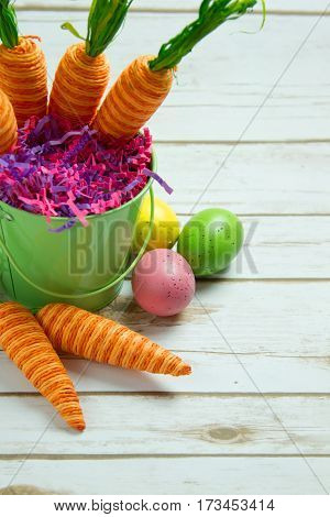 Orange striped faked carrots and colorful Easter Eggs on a rustic whitewashed wood background with room for text