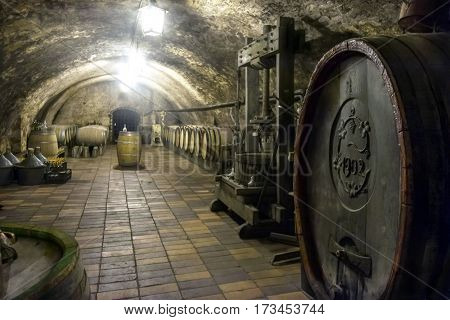 MELNIK, CZECH REPUBLIC - July 18, 2016: Historic arched wine cellar of the Melnik Castle with big aged wine barrel and antique wine press in foreground.