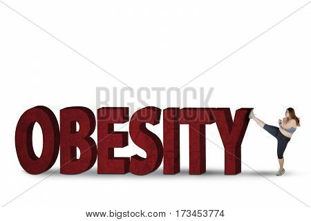 Portrait of young blonde woman kicking word of obesity in the studio, isolated on white background