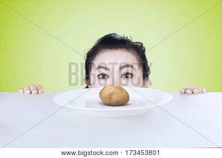 Picture of young woman peeking boiled potato on the table