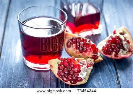 ripe pomergranate with seeds and glass bottle of red juice on wooden table background