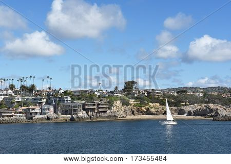 NEWPORT BEACH, CALIFORNIA - FEBRUARY 22, 2017: Sailboat passes by Corona Del Mar homes along the Newport-Avalon Channel in Southern California, viewed from the Newport jetty.