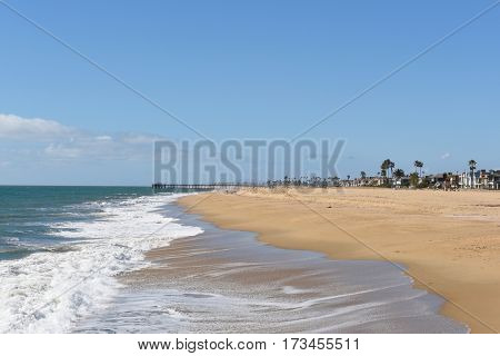 NEWPORT BEACH, CALIFORNIA - FEBRUARY 22, 2017: Balboa Peninsula and Pier. Homes line the beach along the Southern California coastline, viewed from the Newport jetty.