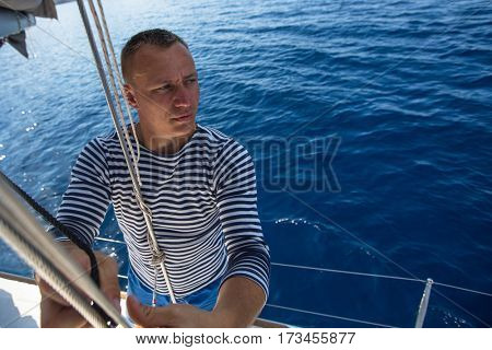 Man holding rope on sailing boat, controlling the sail.