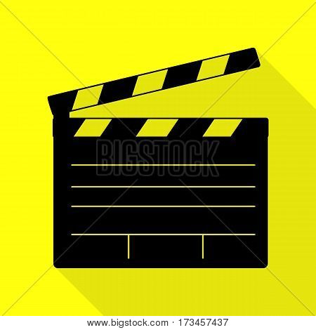 Film clap board cinema sign. Black icon with flat style shadow path on yellow background.