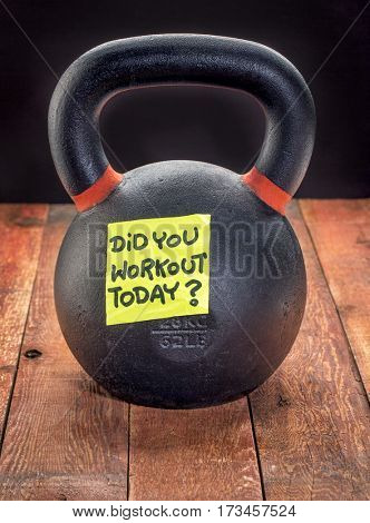 Did you workout today reminder note on a heavy iron kettlebell on a rustic wood background - fitness concept