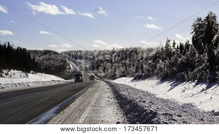 Winter snow scene wide view of cars and trucks on the curving highway to Miramichi, New Brunswick both sides of fir trees covered in thick glittering ice and snow from a recent ice storm. Shot on a chilly bright blue sky sunny day in February.