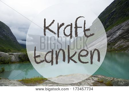 German Text Kraft Tanke Means Relax. Lake With Mountains In Norway. Cloudy Sky. Peaceful Scenery, Landscape With Rocks And Grass. Greeting Card