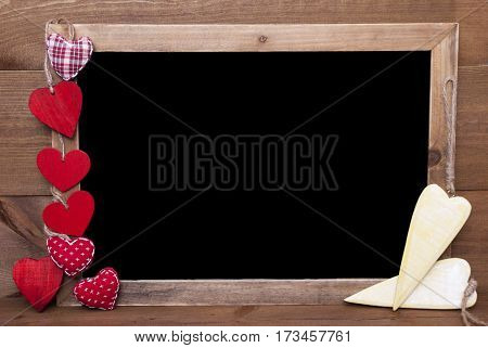 Chalkboard With Copy Space For Advertisement. Red Textile And Wooden Yellow Hearts. Wooden Background With Vintage, Rustic Or Retro Style.