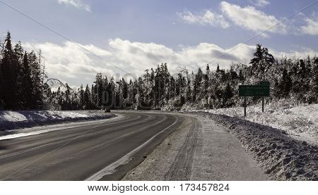 Winter snow scene wide view of the curving highway to Miramichi, New Brunswick both sides of fir trees covered in thick glittering ice and snow from a recent ice storm. Shot on a chilly bright blue sky sunny day in February.