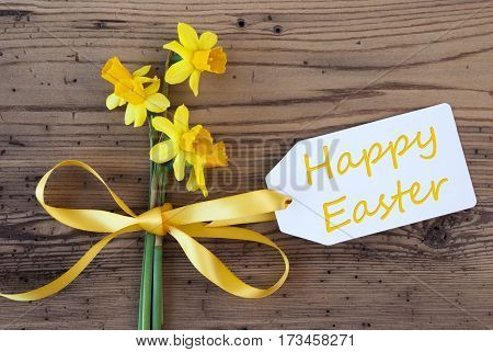 Label With English Text Happy Easter. Yellow Spring Narcissus Or Daffodil With Ribbon. Aged, Rustic Wodden Background. Greeting Card For Spring Season