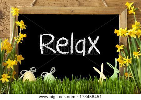 Blackboard With English Text Relax. Spring Flowers Nacissus Or Daffodil With Grass, Easter Egg And Bunny. Rustic Aged Wooden Background.