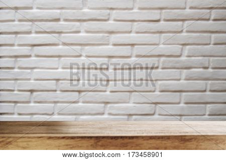 Wooden table top with defocus white bricks wall background