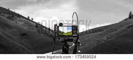 Digital camera on camera tripod taking a photo of green hills landscape, selective focus on camera