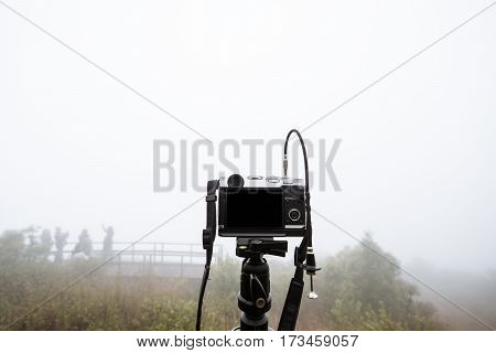 Digital camera on camera tripod, with foggy environment in winter