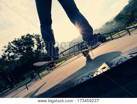 young skateboarder legs practice ollie at skatepark ramp