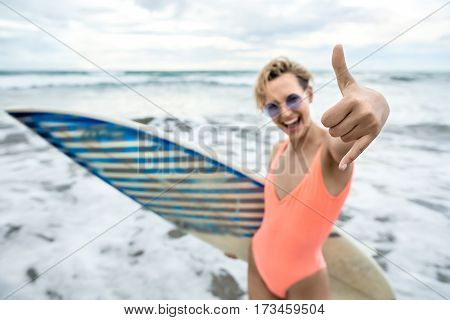 Happy blonde girl stands on the beach on the background of the sea and cloudy sky. She wears orange swimsuit with sunglasses and holds a surfboard. Woman shows thumbs-up gesture. Low aperture photo.