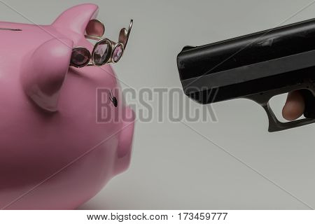 a gun being pointed at a piggy bank