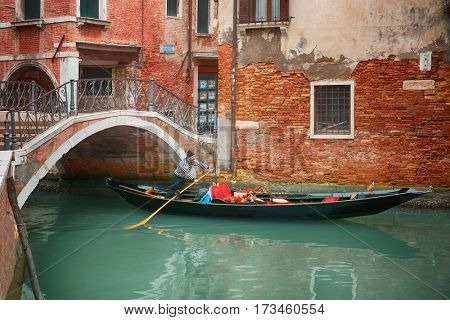 Venice, Italy - Gondolas and canals in Venice, Italy February 17, 2017: Tourists taking photo with gondolier in venetian canal in gondola. Travel (vacation) concept.