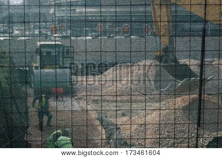 Construction Site Behind Safety Net - Workers Excavator And Roller