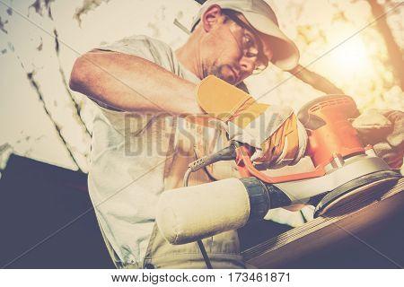 Worker Wood Sanding. Caucasian Men with Wood Sender Machine Sanding Wood Furniture Outdoor.