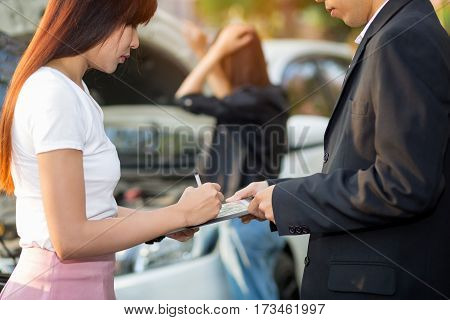 Side view of Asian woman writing on clipboard while insurance agent examining car after accident